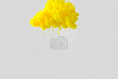 Photo for Close up view of bright yellow paint splash in water isolated on gray - Royalty Free Image