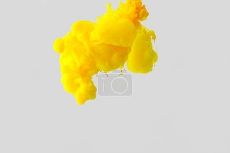 close up view of bright yellow paint splash in water isolated on gray