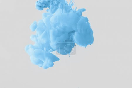 close up view of bright pale blue paint splash in water isolated on gray