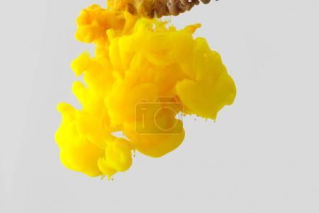 Close up view of bright yellow ink  splash in water isolated on gray