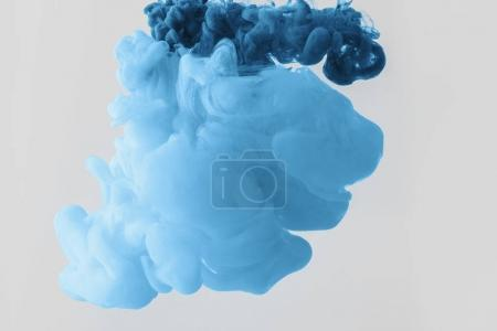 close up view of mixing of bright pale blue and blue paints splashes  in water isolated on gray