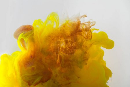 Photo for Close up view of mixing of yellow and brown ink splashes in water isolated on gray - Royalty Free Image