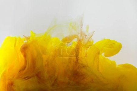 Photo for Close up view of mixing of yellow and brown inks splashes in water isolated on gray - Royalty Free Image