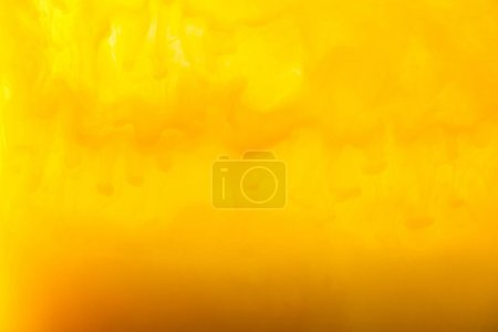 full frame image of mixing of yellow and brown paints splashes in water
