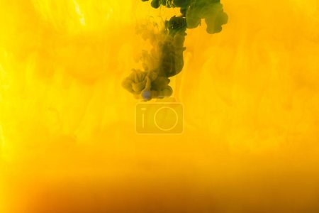 Photo for Full frame image of mixing of yellow and green paints splashes  in water - Royalty Free Image