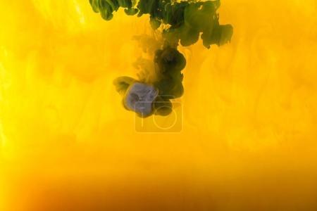 Photo pour Image plein cadre de mélange des éclaboussures de peinture jaune, vert et violet dans l'eau - image libre de droit