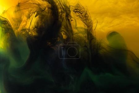 Photo for Full frame image of mixing of yellow, green and black paints splashes  in water - Royalty Free Image