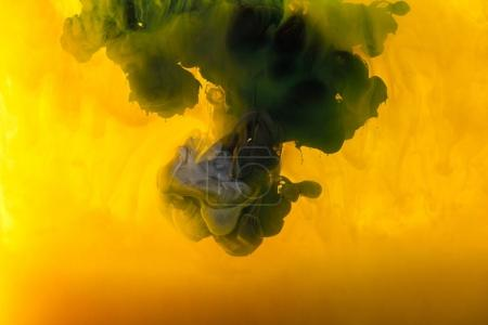 full frame image of mixing of yellow, green and black paints splashes  in water
