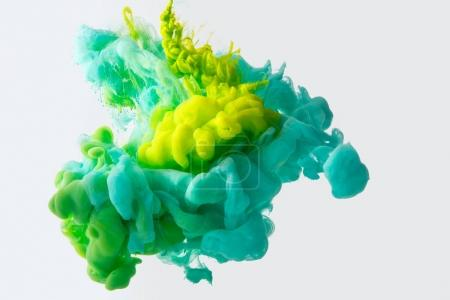 Close up view of mixing of green, yellow and bright turquoise inks splashes in water isolated on gray