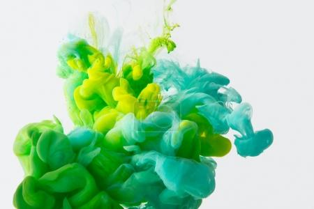 Photo for Close up view of mixing of green, yellow and bright turquoise inks splashes in water isolated on gray - Royalty Free Image