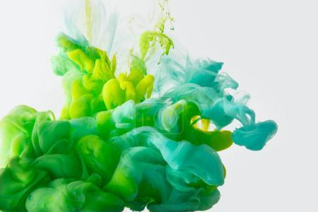 Photo for Close up view of mixing of green, yellow and bright turquoise paints splashes in water isolated on gray - Royalty Free Image