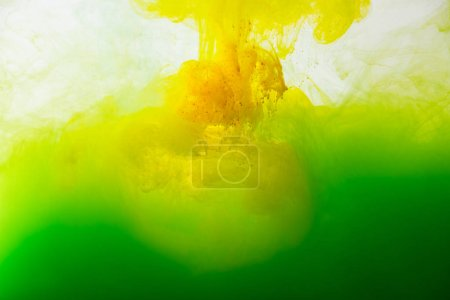 close up view of mixing of green and yellow paints splashes in water isolated on gray