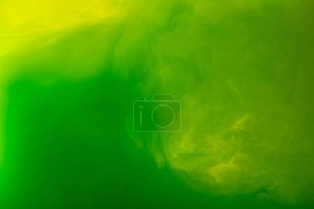 full frame image of mixing of green and yellow paints splashes in water isolated on gray