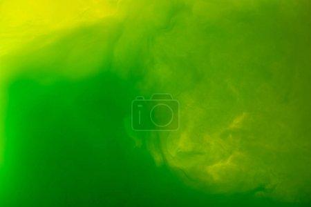 Photo pour Image plein cadre de mélange de vert et jaune peint des projections dans l'eau isolé sur gris - image libre de droit