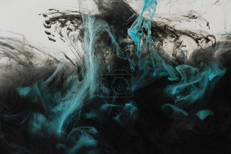 Foto de Cerrar vista de mezcla de toques de luz gris, turquesa y negro pinturas en agua aislado en gris - Imagen libre de derechos