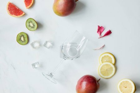 flat lay with empty wineglass, flower petals, ice cubes and assorted exotic fruits on white tabletop