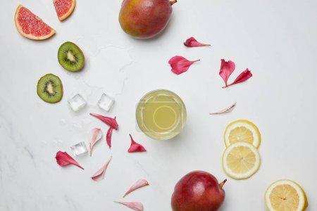 Photo pour Plat avec cocktail d'alcool, glaçons, fruits exotiques disposés et pétales de fleurs sur la surface blanche - image libre de droit