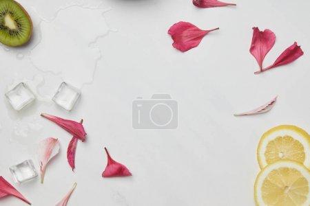 Photo pour Pose plate avec des pétales de fleurs, des glaçons, des morceaux de citron et de kiwi sur la table blanche - image libre de droit