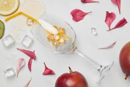 top view of arrangement of exotic fruits, flower petals, wineglass with straw and ice cubes on white surface