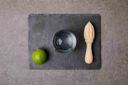 flat lay with wooden squeezer, fresh lime and empty glass on grey surface