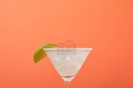 close up view of refreshing alcohol margarita cocktail with lime and ice isolated on orange