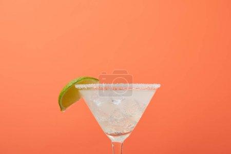 Nahaufnahme des erfrischenden Alkohol-Margarita-Cocktails mit Limette und Eis isoliert auf Orange