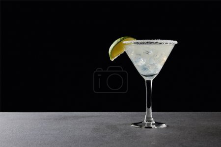 Nahaufnahme von leckerem Margarita-Cocktail mit Limette und Eis auf Tischplatte auf schwarz