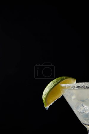 Close up view of cold margarita cocktail with lime isolated on black