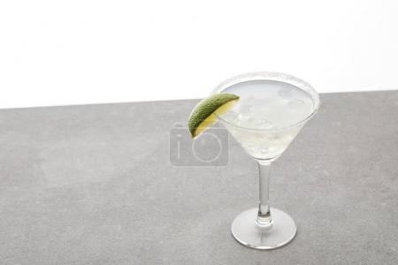 close up view of refreshing alcohol margarita cocktail with lime and ice on tabletop on white