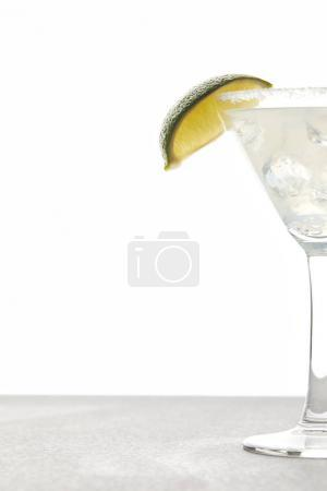 close up view of refreshing margarita cocktail with lime piece and ice on tabletop on white