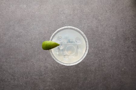 top view of alcohol margarita cocktail with lime piece and ice on grey surface