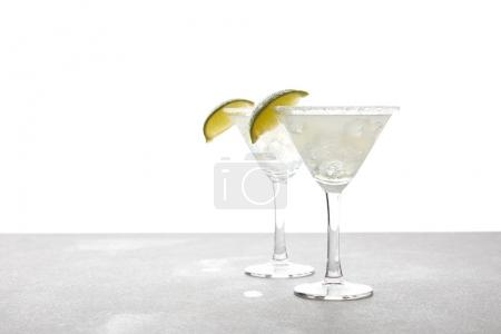 Photo for Close up view of alcohol margarita cocktails with lime on grey surface on white - Royalty Free Image