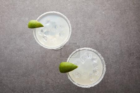 top view of cold alcohol margarita cocktails with pieces of lime on grey tabletop