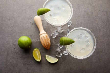 flat lay with margarita cocktails with pieces of lime, ice cubes and wooden squeezer on grey tabletop