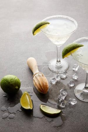 Photo for Close up view of alcohol cocktails with pieces of lime, ice cubes and wooden squeezer on grey tabletop - Royalty Free Image