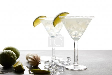 Photo for Close up view of margarita cocktails with lime pieces and wooden squeezer on grey surface on white - Royalty Free Image