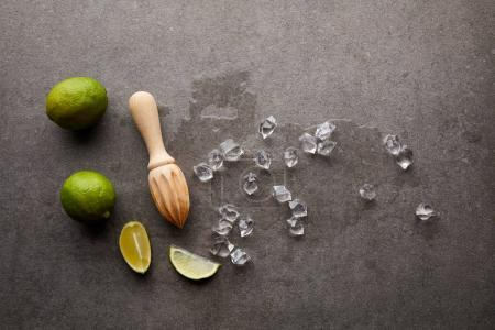 flat lay with wooden squeezer, limes and ice cubes for cocktail on grey surface