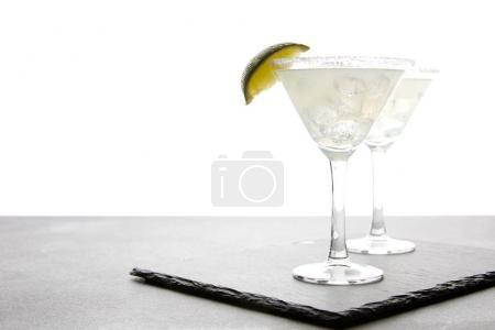 close up view of alcohol cocktails with lime on grey surface on white