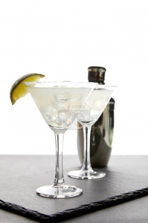 close up view of alcohol margarita cocktails with lime and shaker on grey surface on white