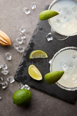 top view of alcohol margarita cocktails with pieces of lime, ice cubes and wooden squeezer on grey tabletop