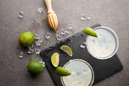 Photo for Top view of margarita cocktails with pieces of lime, ice cubes and wooden squeezer on grey tabletop - Royalty Free Image
