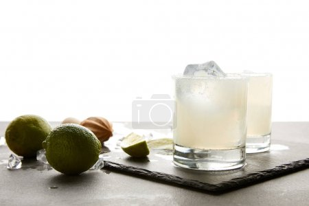 close up view of refreshing sour alcohol cocktails with lime and ice on tabletop on white