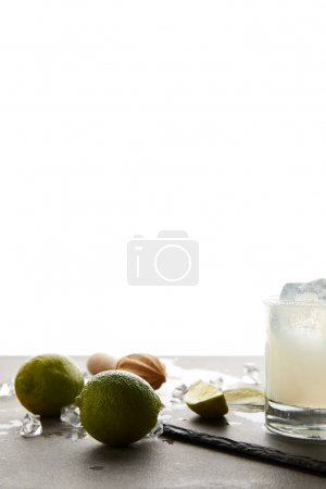close up view of refreshing sour caipirinha cocktail with lime on tabletop on white