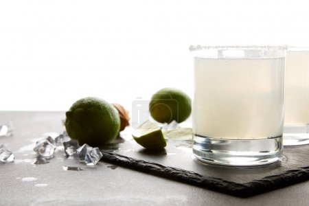 Close up view of refreshing margarita cocktails with lime on tabletop on white