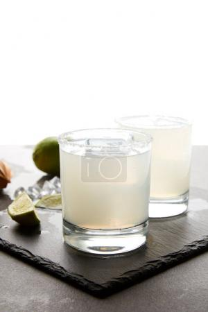 Close up view of refreshing caipirinha cocktails with lime on tabletop on white