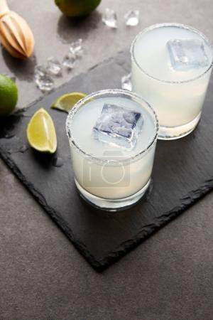 Photo pour Vue rapprochée du pressoir en bois, cocktails caipirinha aigre rafraîchissants avec citron vert et glace sur la table grise - image libre de droit