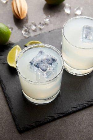 Photo pour Bouchent la vue de presse-citron en bois, des cocktails alcool aigre au citron vert et glace sur le dessus de table gris rafraîchissants - image libre de droit