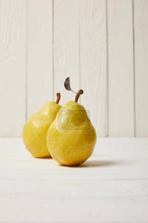 two yellow organic pears on wooden background