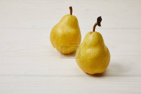 two fresh yellow pears on wooden background