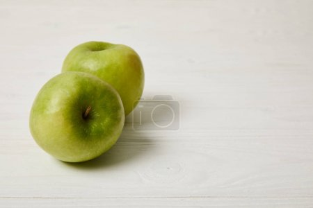 raw fresh green apples on wooden background